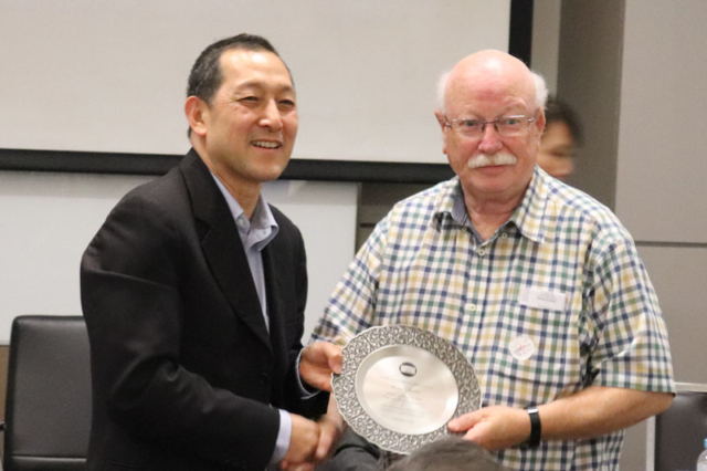 Gary Brown receives a Pewter Plate form the FIP Vice President